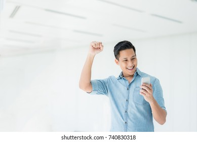 Happy excited Asian man looking at his smartphone and raising his arm up to celebrate success or achievement.