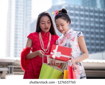 Happy excited Asian woman in chinese dress open Gift box on background city centre. chinese new year and shopping concept - Shutterstock ID 1276537765