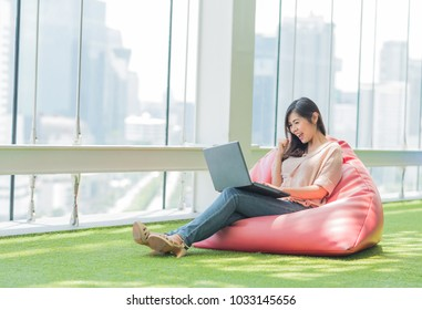 Happy excited Asian woman sitting on beanbag using laptop and raising his arm up to celebrate success or achievement.