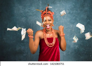 happy and excited beautiful nigerian lady dressed in traditional edo bridal attire showered with money