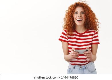 Happy excited beautiful redhead curly girl having fun playing awesome smartphone game holding cellphone horizontal look camera grinning playfully check out cool new app adore application