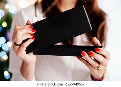 Happy excited beautiful young woman opening jewelry gift box. Christmas gift