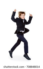 Happy excited boy in school uniform jumping for joy. Isolated over white background. School fashion. Copy space.