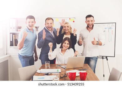 Happy excited business people celebrate success looking at laptop screen in the office. Successful corporate team of partners and coworkers, winners