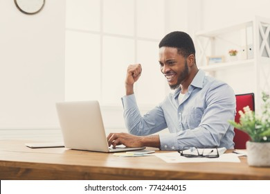 Happy excited businessman celebrate his success. Winner, black man in office reading on laptop, copy space