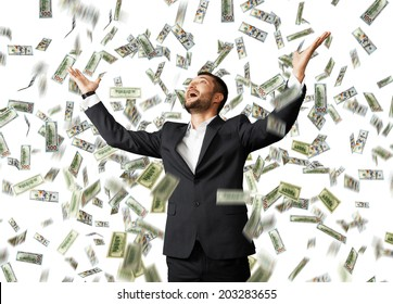 happy excited businessman raising hands up and looking up under money rain