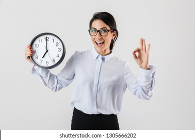 Happy excited businesswoman smartly dressed standing isolated over white background, showing alarm clock