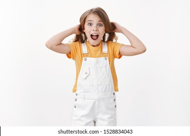 Happy excited child having fun, standing playful and surprised, girl touching hair lifting haircut in air, shouting amused and joyful, express enthusiastic cheerful mood, stand white background