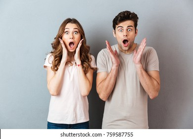 Happy excited couple standing with hands at their face and looking at camera over gray wall