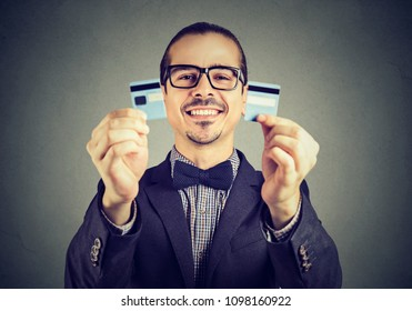 Happy excited debt free business man in glasses holding a credit card cut in two pieces