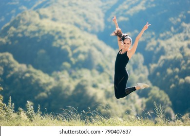 Happy Excited Fitness Woman Raising Arms Celebrating with Victory Sign. Fitness girl celebrating victory outdoors in wonderful natural decor