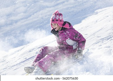 Happy and excited girl Sledding downhill on a snowy day.Cute girl laughing and showing excitement while she slides downhill while snow sledding on a winter day outdoors