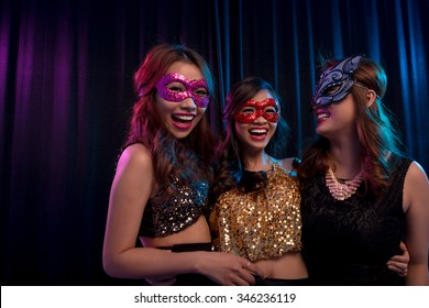Happy excited girls wearing masquerade ball masks