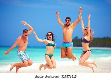 happy excited group of young friends jumping on summer beach