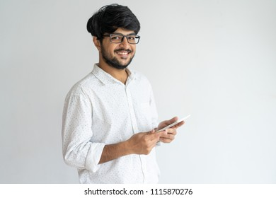 Happy excited Indian male entrepreneur using gadget while monitoring information. Cheerful optimistic young businessman in glasses working with modern device. Successful man concept