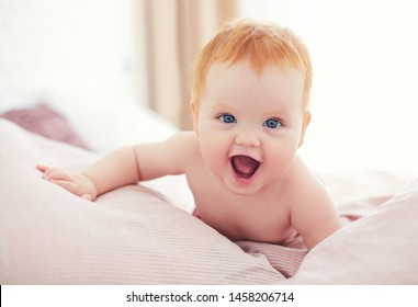 happy excited infant baby girl crawling on the bed