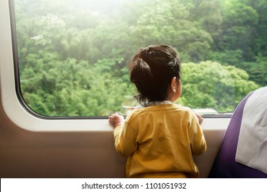 Happy and Excited Kids Traveling by Train. A Two Years old Girl Looking through Wide Glass Window. Green Forest as Outside View