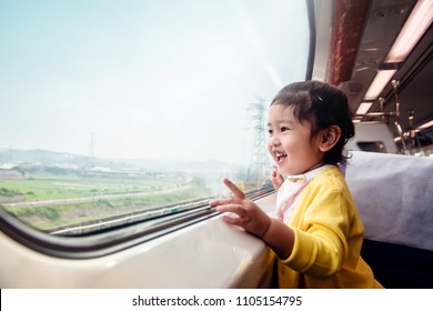 Happy and Excited Kids Traveling by Train. A Two Years old Girl Pointing her hand to Outside View, Sitting Near Wide Glass Window and Smiling