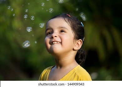 happy excited little girl playing with water bubbles