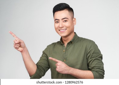 Happy excited man pointing away at copy space with two fingers isolated over white background
