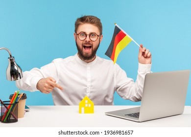 Happy excited man pointing finger at toy paper house holding flag of germany in hand, moving into another country, sitting at workplace with laptop. Indoor studio shot isolated on blue background