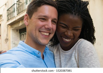 Happy excited mix raced couple having fun outside. Closeup of young man and woman standing in old town street, looking away, smiling, laughing. Dating couple concept