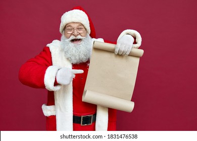 Happy excited old bearded Santa Claus wearing costume holding Merry Christmas wishlist paper roll pointing finger at blank empty xmas wish list letter standing isolated on red background, copy space.