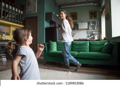 Happy excited smiling fit single mother running with little preschool cute daughter in living room at home, babysitter playing with girl, pupil, family spending time together, having fun