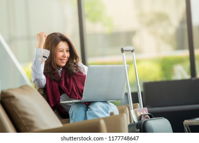 Happy excited successful businesswoman triumphing with laptop. Asian elegant businesswoman working on laptop in airport hall. Woman waiting her flight at airport terminal.