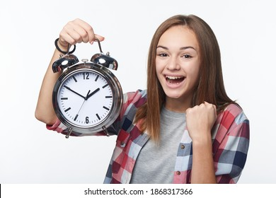Happy excited winning successful teen girl holding big alarm clock screaming, isolated over white background. Time concept