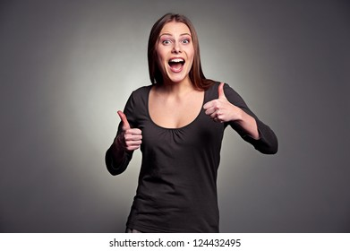 happy excited woman showing thumbs up over dark background