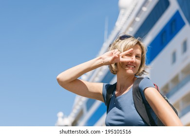 Happy excited woman tourist dancing of joy, in front of big cruise liner, summer day