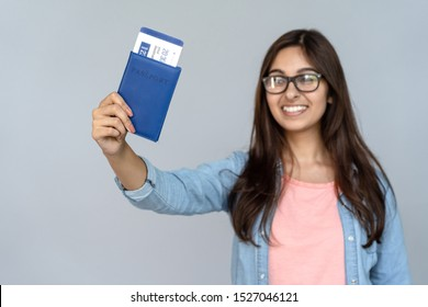 Happy excited young adult Indian woman student holding passport with airplane flight ticket boarding pass standing isolated on grey background with copy space, travel by plane, study abroad concept