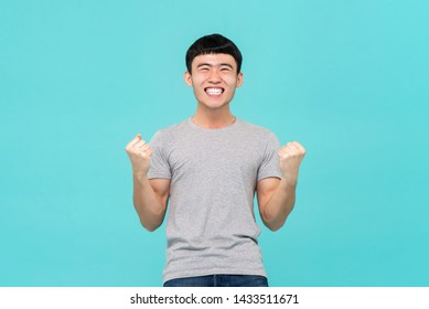 Happy excited young Asian man raising his fists doing yes gesture celebrating success