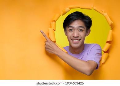 Feliz entusiasmado joven adolescente asiático posa a través de un agujero de papel amarillo roto señalando un espacio de copia o papel amarillo en blanco, usando camiseta morada, publicitando el mejor producto. Negocio de publicidad.