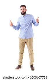 Happy excited young bearded man showing thumbs up and smile at camera. Full body length portrait isolated on white studio background.
