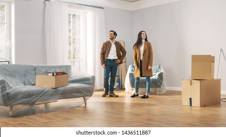 Happy and Excited Young Couple Look Around In Wonder at their Newly Purchased / Rented Apartment. Beautiful People Poses Happily. Big Bright Modern Home with Cardboard Boxes Ready to Unpack.