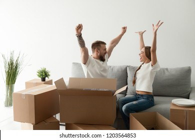Happy excited young couple sitting together on couch, sofa celebrating moving at new house with cardboard boxes with belongings, family just arrived in new home, man and woman start living together