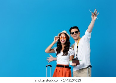 Happy excited young couple tourists holding passports and boardingpasses ready for travel isolated on blue background with copy space