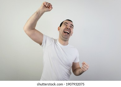 happy excited young male man stand closeup white background laugh hand up crazy look angry