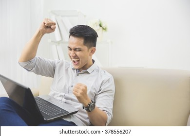 happy excited young man with laptop at home sitting on a couch