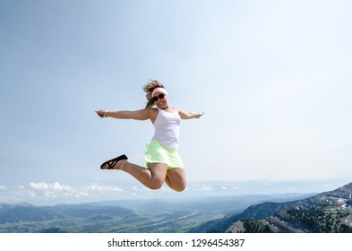Happy excited young woman jumps on top of the Grand Teton Mountains in Jackson Hole Wyoming in the summer. Concept for freedom, travel