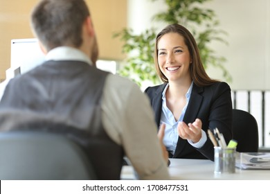 Happy executive coworkers laughing and talking sitting on a desk at the office