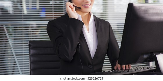 a happy executive wearing suit calling customer service on the phone and sitting on a desk in the office
