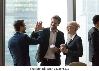 Happy executives have fun give high five during friendly talk in office, cheerful employees laugh celebrate funny joke, share success and good teamwork result motivated by great corporate relations