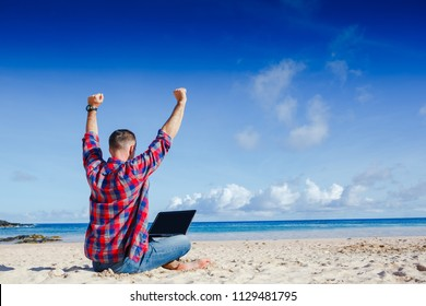 Happy exited man with raised hands up celebrate success in job or great news in front of laptop