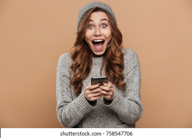 Happy exited pretty girl in gray knitted hat and warm sweater holding mobile phone and looking at camera, isolated on beige background