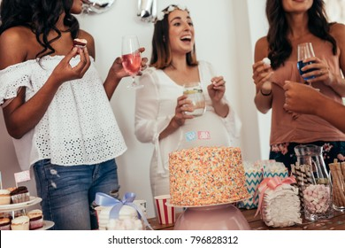 Happy expecting mother at baby shower with friends. Group of women having food and drink at baby shower party.