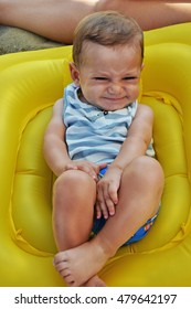 Happy expressive baby boy on inflatable yellow ring