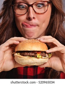 Happy and expressive nerd woman eating burger.Sticking out tongue.